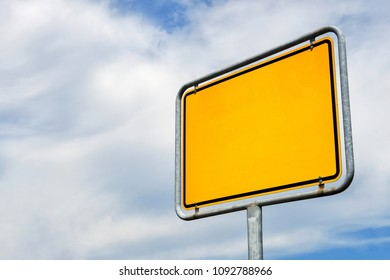 Blank yellow city sign in Germany. Template with copy space isolated on blue sky and clouds.