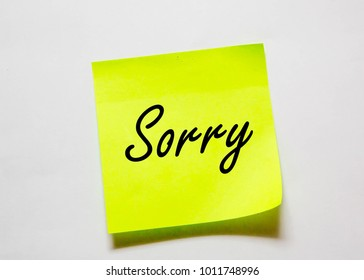 "A blank yellow coloured sticky note pad isolated with the message of ""Sorry"" on an off white background"
