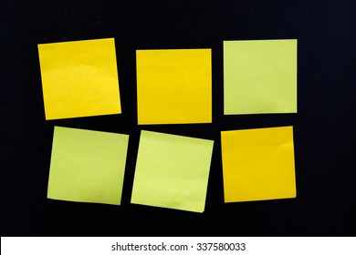 Blank yellow note paper set on black background