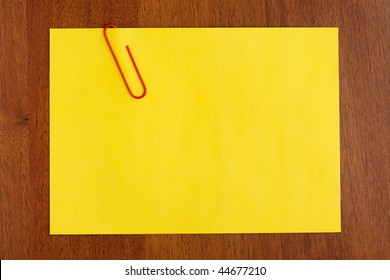 Blank yellow note with red clip on wooden background. Just add your text
