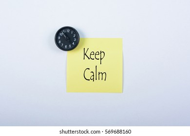 Blank yellow notepad with black magnetic watch isolated on white background. Keep Calm