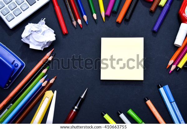 Blank yellow pink post-it note on blackboard surrounded by stationery.