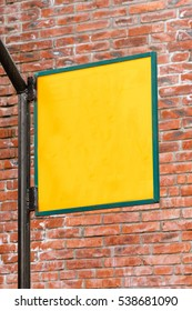 Blank yellow signboard on brick wall background