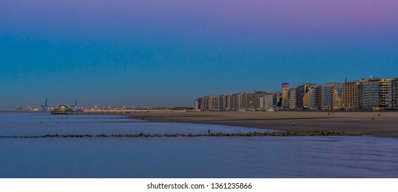 Blankenberge beach with view on the city and jetty, lighted architecture by night, popular coast of belgium