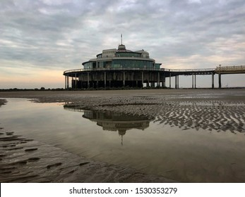 Blankenberge, Belgium - 13 October 2019: iconic well-known historic sea pier in Blankenberge beach at low tide on the North Sea with a cloudy sky in the morning evening