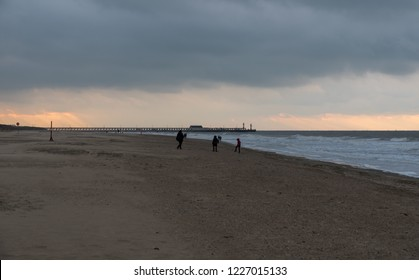 Blankenberge, Flanders / Belgium - 10 30 2018: A few kids playing at an empty sandy beach at the Belgian North sea