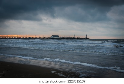 Blankenberge, Flanders / Belgium - 10 30 2018: Rain clouds coming over the Belgian North sea with a pier in the background