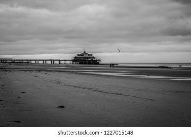 Blankenberge, Flanders / Belgium - 10 30 2018: Empty sandy beach and pier at the Belgian North sea during ebb tide in autumn.