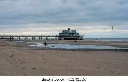 Blankenberge, Flanders / Belgium - 10 30 2018: Large sandy beach and pier at the Belgian North sea during ebb tide in autumn.