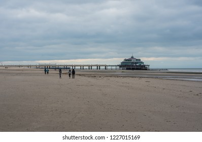 Blankenberge, Flanders / Belgium - 10 30 2018:Young girls walking over a sandy beach at the Belgian North sea with a pier in the background