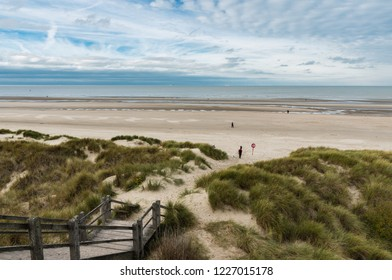 Blankenberge, Flanders / Belgium - 10 30 2018: Wooden staircase to sandy beach and green dunes at the Belgian North sea during ebb tide in autumn.