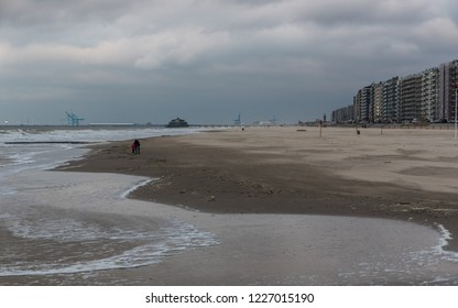 Blankenberge, Flanders / Belgium - 10 30 2018: Line of second residence apartment blocks and a large sandy beach at the Belgian North Sea
