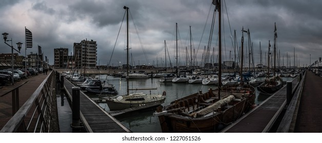 Blankenberge, Flanders / Belgium - 10 30 2018: Wide panoramic view over the small sea harbor with rainy clouds in the background