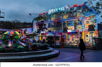 Blankenberge, Flanders / Belgium - 10 30 2018: Adults and children having fun at the fair in the rain by night