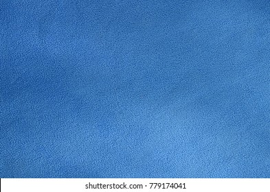 The blanket of furry blue fleece fabric. A background texture of light blue soft plush fleece material