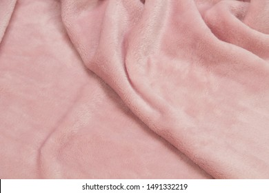 The blanket of furry fleece fabric. A background soft plush fleece material with a lot of relief folds