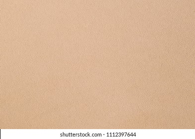 The blanket of furry orange fleece fabric. A background texture of light orange soft plush fleece material