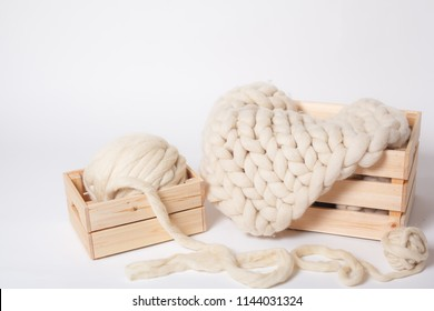 Blanket made of thick Merino yarn and wool balls in wooden boxes on white background.