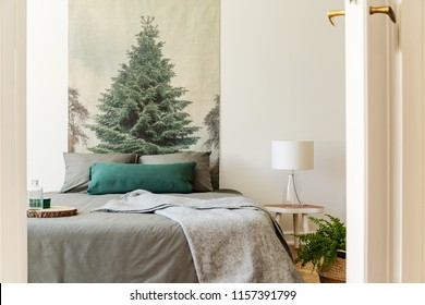 Blanket on grey bed in hotel bedroom interior with tree painting and lamp on table. Real photo