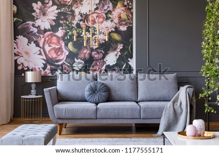 Blanket on grey couch in living room interior with flowers wallpaper and  lamp on table. f8e3ac7b4