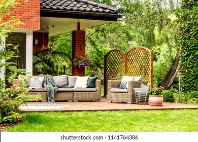 Blanket thrown on garden sofa and basket with pillows standing next to armchair on wooden terrace