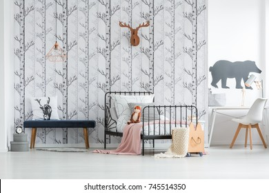 Blanket thrown on wooden basket with wheels standing next to metal bed in children's bright room with desk