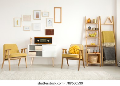 Blankets on a ladder near wooden yellow armchairs and white cupboard with radio in vintage flat interior with posters