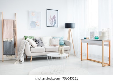 Blankets on a ladder and white table on a carpet in living room with lamp and cushions on a sofa