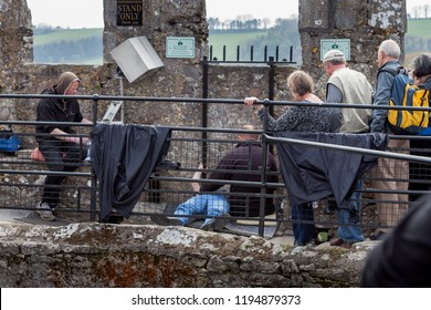 Blarney Castle, Ireland - April 20,2011: People line up to kiss the Blarney Stone at Blarney Castle near Cork in Ireland. Kissing the Blarney Stone is supposed to help you gain the gift of eloquence.