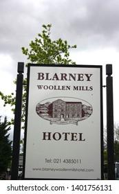 Blarney, County Cork, Republic of Ireland - May 6, 2019: Sign for Blarney Woollen Mills Hotel with a tree and sky in the background