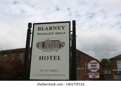 Blarney, County Cork, Republic of Ireland - May 3, 2019: Sign providing information for Blarney Woollen Mills Hotel with an additional sign, building, and cloudy sky in the background