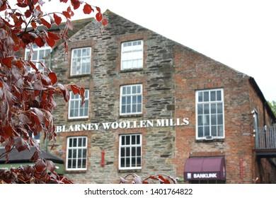 Blarney, County Cork, Republic of Ireland - May 3, 2019: Blarney Woolen Mills framed by foliage from a purple autumn ash tree