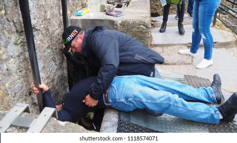 Blarney / Ireland - May 19, 2018: The contortion required to kiss the Blarney Stone at Blarney Castle, Blarney, Ireland, May 19, 2018.