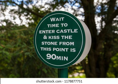 Blarney, Republic of Ireland - August 16th 2018: A sign informing visitors that the wait time to kiss the Blarney Stone at the historic Blarney Castle is 90 minutes.