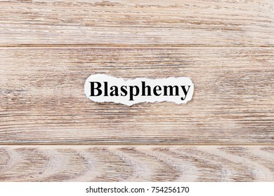 BLASPHEMY of the word on paper. concept. Words of BLASPHEMY on a wooden background.