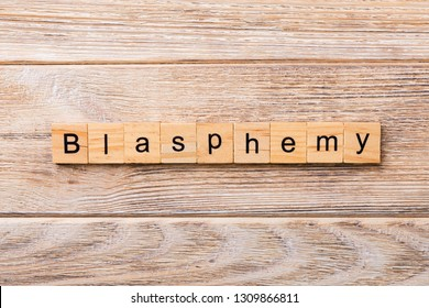 BLASPHEMY word written on wood block. BLASPHEMY text on wooden table for your desing, concept.