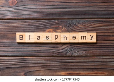BLASPHEMY word written on wood block. BLASPHEMY text on cement table for your desing, concept.