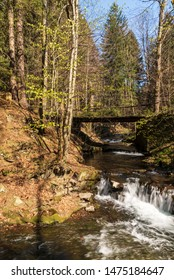 Blatny potok creek above Moravka village with small water cascades, bridge above, trees around and clear sky in Moravskoslezske Beskydy mountains in Czech republic