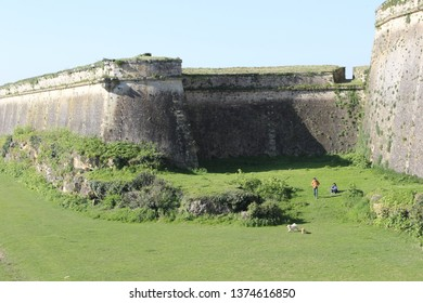 "BLAYE, FRANCE-MAR. 27, 2019:  A couple play with their dogs in the ""moat"" at Blaye citadel.  Never a real moat as there was no water, it was used in medieval times as agricultural land."