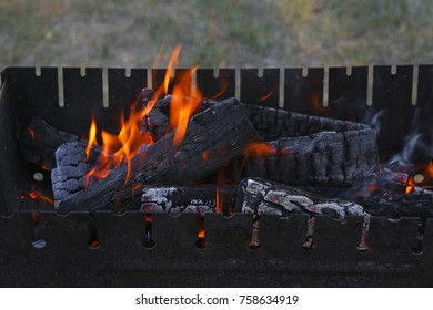 Blaze of bonfire, wood fire flame heat spires burning in bbq grill fireplace with smoke close up