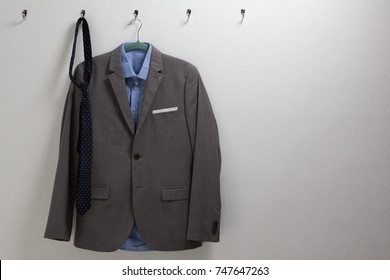 Blazer hanging on hook against wall