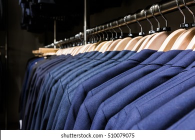 Blazer Jacket on Rack in Store Men Fashion Wooden Hangers Clothes Suit Professional Luxury Many Multiple Closeup