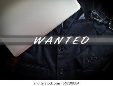 Blazer and laptop on dark background, business and education concept with word WANTED
