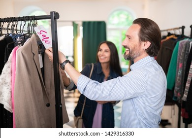 A blazer with sale tag. Smiling appealing handsome attractive cheerful dark-haired man looking at the blazer with sale tag in the showroom