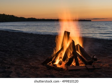 Blazing Bonfire on the Beach at Sunset
