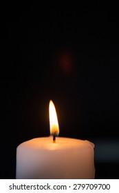 Blazing candle on black background