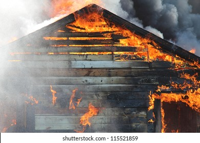 A blazing fire burns through the roof rafters of an old farm home.
