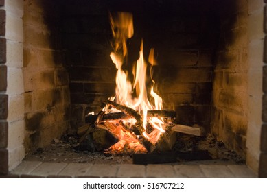 Blazing fireplace. Fireplace in action. Burning of wood and coal. Fireplace as part of the interior
