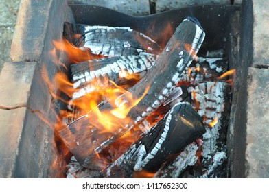 Blazing firewood with black cracked surface covered with white gray ashes. Old charred bricks in charcoal mangal. Burning wood logs texture with red flames. Fiery background. Barbecue grill concept.