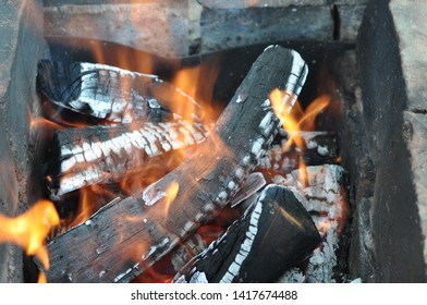 Blazing firewood with black cracked surface covered with white ashes. Inside view to old charcoal mangal. Charred wood logs texture with flames. Fiery background. Grunge brazier for barbecue. .